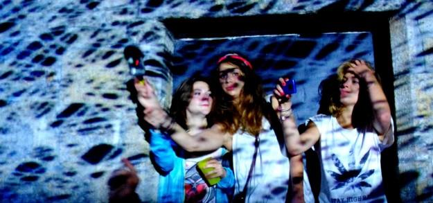 Quelques jeunes filles dansent dans l'encadrement d'une fenêtre du Manoir de Keroual. Astropolis 2013. Crédits La Déviation